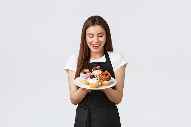 식료품점 직원, 중소기업 및 커피숍 개념. 쾌활한 바보 웨이트리스는 맛있는 컵 케이크를 먹고 싶어합니다. 바리스타가 새로운 디저트, 흰색 배경을 맛보고 싶어 입술을 깨물고 있습니다.