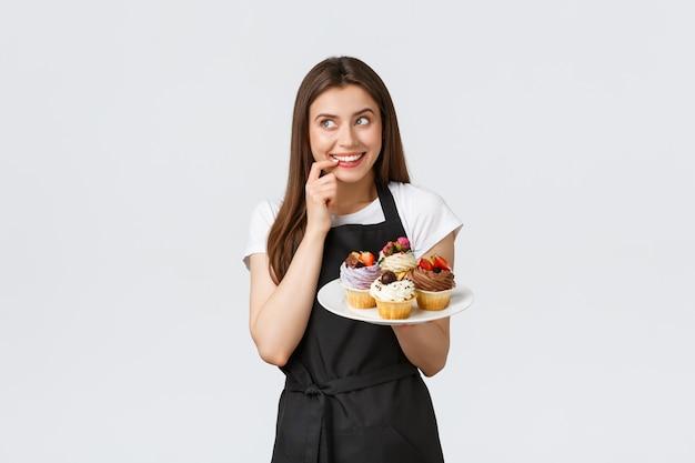 Работники гастронома, концепция малого бизнеса и кафе. веселая глупая официантка хочет перекусить вкусными кексами. бариста кусает губу, заманчиво пробуя новые десерты
