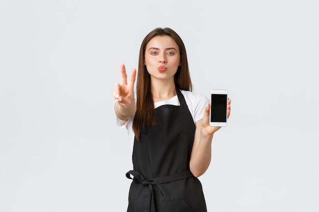Работники продуктового магазина, малый бизнес и концепция кафе. симпатичная глупая женщина-бариста в черном фартуке показывает знак мира, целует губы и показывает мобильный телефон, рекламирует приложение