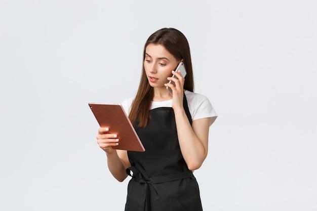 Работники гастронома, концепция малого бизнеса и кафе. милая улыбающаяся продавщица в черном фартуке подтверждает заказ, разговаривает с клиентом по телефону и смотрит на цифровой планшет