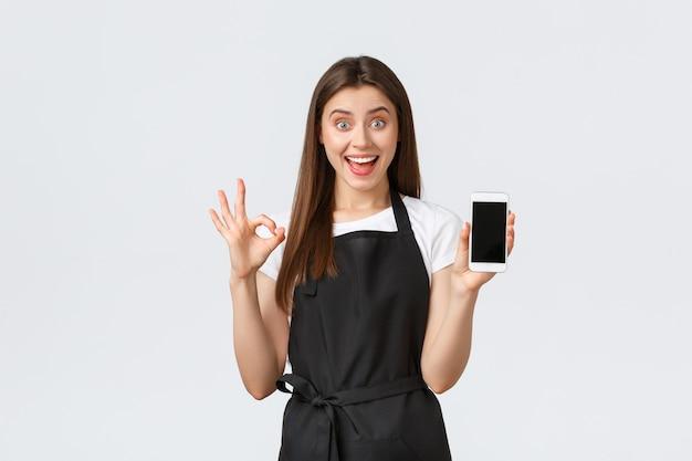Работники продуктового магазина, малый бизнес и концепция кафе. взволнованная довольная женщина-бариста в черном фартуке гарантирует хороший пользовательский опыт, показывая приложение на экране смартфона, делайте знак