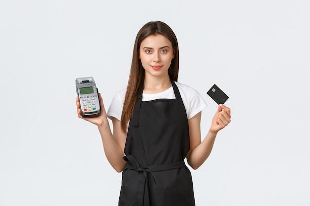Работники продуктового магазина, малый бизнес и концепция кафе. приветливая милая кассирша, продавщица в черном фартуке, показывающая кредитную карту и pos-терминал, удобная бесконтактная оплата в магазине