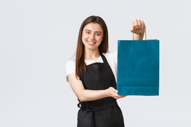 Работники продуктового магазина, малый бизнес и концепция кафе. дружелюбная, услужливая, улыбающаяся продавщица передает покупателю сумку с покупкой, клерк или кассир обрабатывает заказ.