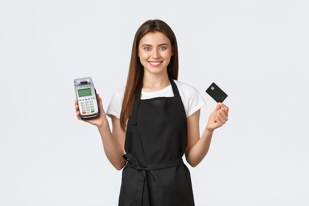 Работники продуктового магазина, малый бизнес и концепция кафе. приветливый улыбающийся кассир, женщина-бариста в черном фартуке показывает pos-терминал и кредитную карту для бесконтактной безопасной оплаты.