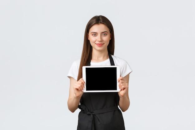 Работники продуктового магазина, малый бизнес и концепция кафе. приветливая улыбающаяся милая бариста в черном фартуке представляет промо-скидки на экране цифрового планшета. продавщица предоставит информацию.