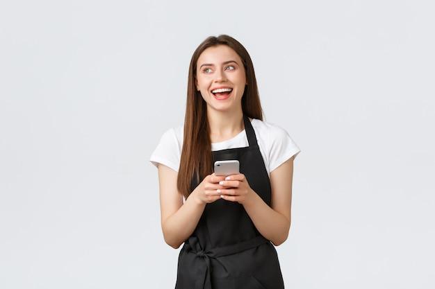 Работники гастронома, концепция малого бизнеса и кафе. счастливая красивая женщина-бариста, официантка в кафе в черном фартуке, смеется и смотрит налево, используя мобильный телефон