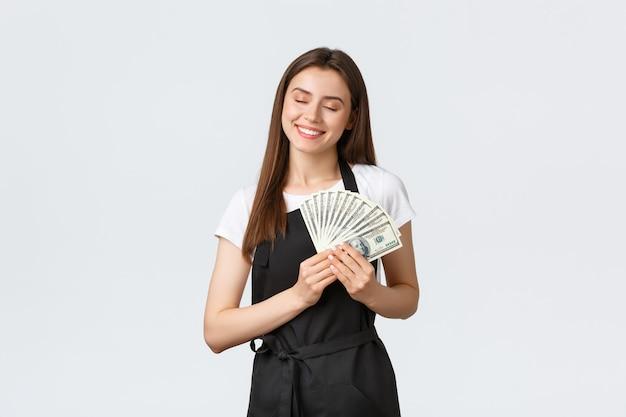 Работники продуктового магазина, малый бизнес и концепция кафе. счастливый улыбающийся женский бариста обнимает ее зарплату или чаевые, обнимает деньги с закрытыми глазами и удовлетворением на лице.