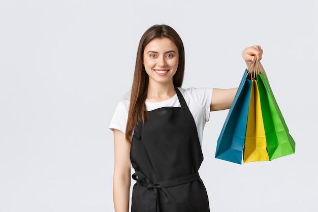 Работники продуктового магазина, малый бизнес и концепция кафе. прекрасная продавщица в черном фартуке, держащая бумажные пакеты с заказом клиента, улыбаясь, как висит над покупкой, работает кассиром.