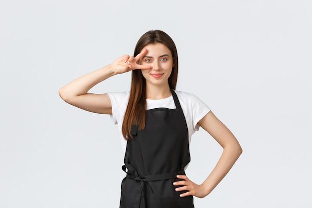 Работники продуктового магазина, малый бизнес и концепция кафе. оптимистичный дружелюбный милый бариста в черном фартуке показывает знак мира поверх глаз и улыбается, приглашая посетителей в кафе или ресторан