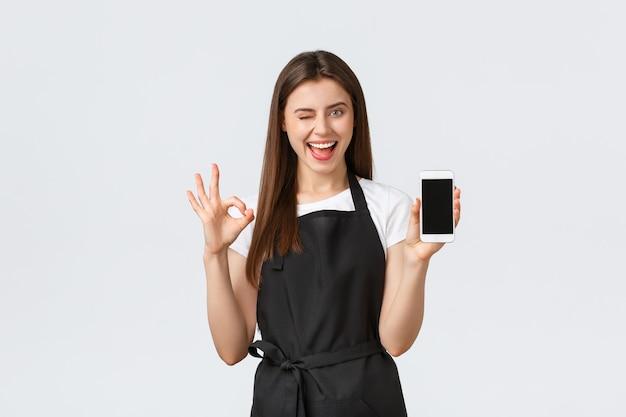 Работники продуктового магазина, малый бизнес и концепция кафе. довольная красивая девушка-бариста в черном фартуке показывает знак ок и дисплей мобильного телефона, рекомендую классное приложение