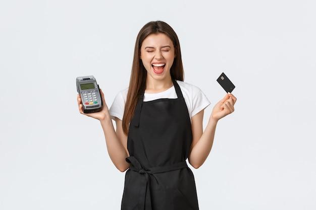 Работники продуктового магазина, малый бизнес и концепция кафе. улыбающийся беззаботный кассир закрывает глаза и радостно улыбается, стоя с pos-терминалом и кредитной картой, белый фон