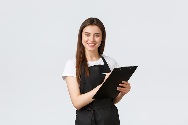 Работники гастронома, концепция малого бизнеса и кафе. улыбающийся дружелюбный менеджер магазина в черном фартуке записывает информацию в буфер обмена, стоя на белой стене