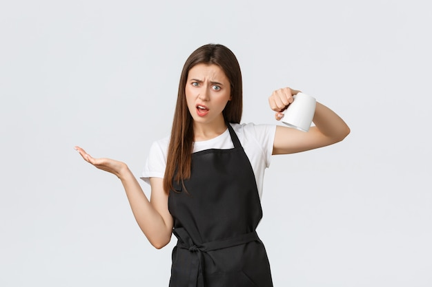 Grocery store employees, small business and coffee shops concept. confused female barista showing empty cup and looking puzzled, shrugging upset that drink finished fast