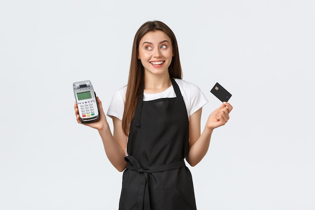Grocery store employees small business and coffee shops concept dreamy cute smiling waitress looking away at banner while holding credit card and pos terminal for contactless payment