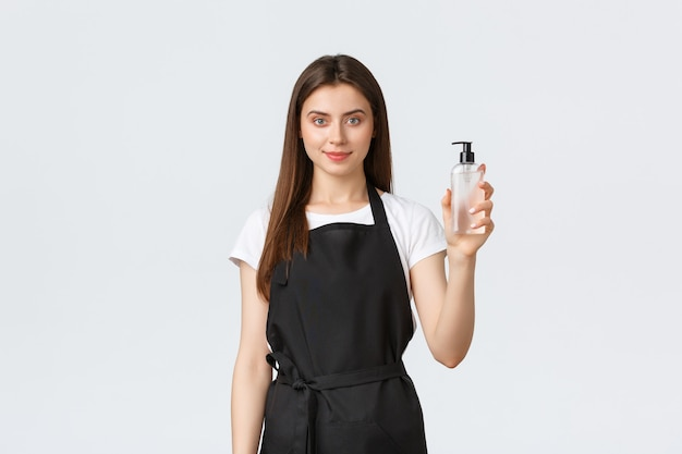 Grocery store employees, small business and coffee shops concept. excited pleased female barista in black apron guarantee good user experience showing smartphone display application, make okay sign.