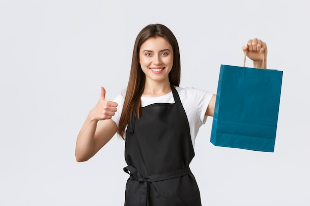 Grocery store employees, small business and coffee shops concept. friendly cute saleswoman packing your gift or purchased items in paper bag, showing thumbs-up and smiling