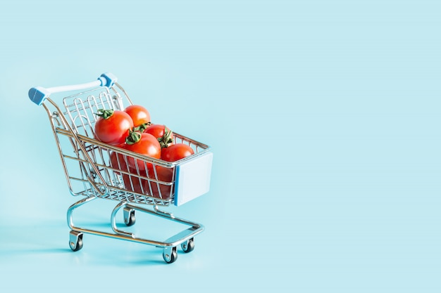 Grocery trolley with tomatoes on blue.