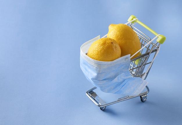 파란색 배경에 보호 마스크에 두 개의 레몬, 코로나 바이러스 대유행 covid-19 동안 쇼핑의 위험 개념, 텍스트를위한 공간과 식료품 트롤리