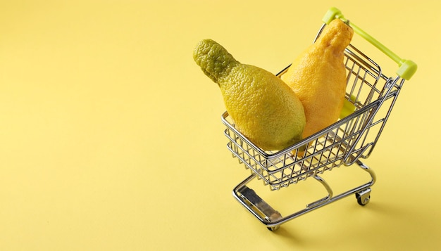Grocery trolley with two ugly lemons on bright yellow table. concept environmental shopping, organic food