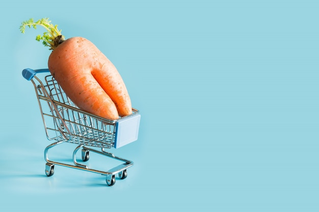 Grocery trolley with ugly carrot on blue.