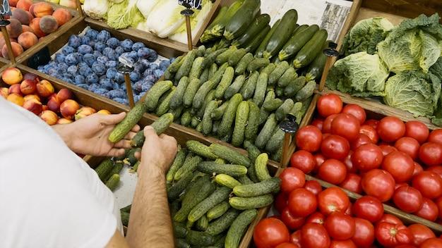 Бакалейщик раскладывает органические огурцы на полках магазинов. продавец заполняет стеллажи для хранения овощей и фруктов в супермаркете.