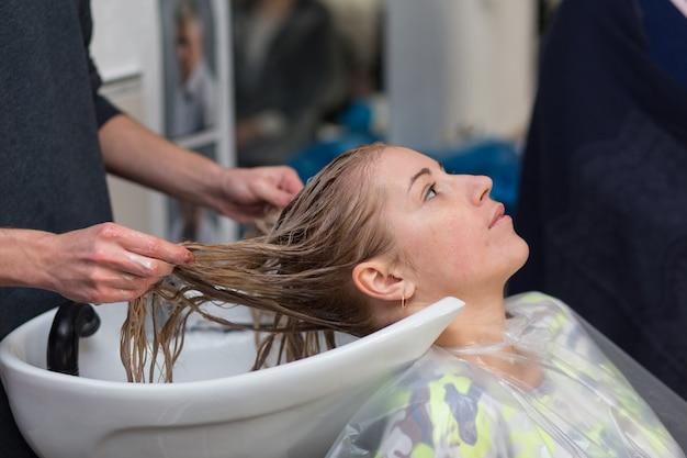 Гродно, беларусь - 20 октября 2016: технолог бренда keune артем райчук красит волосы модели на рекламном семинаре с участием в салоне красоты «колибри».