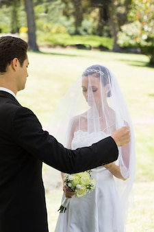 Groom about to lift veil of bride