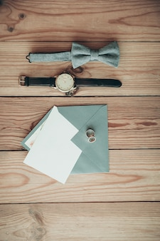 Groom accessories for wedding day – watch, bow tie, rings, envelope with copy space card