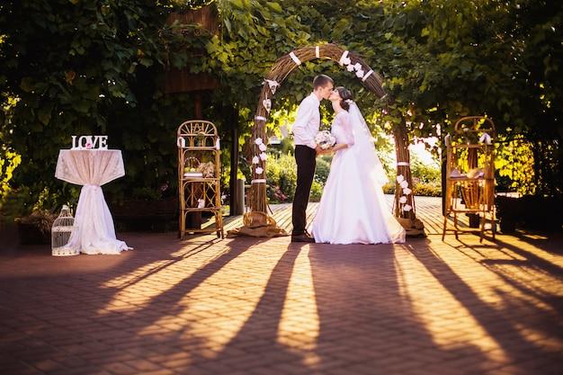 신랑과 신부 버드 나무 가지의 웨딩 아치의 배경에 하얀 드레스를 입고. 웨딩 사진