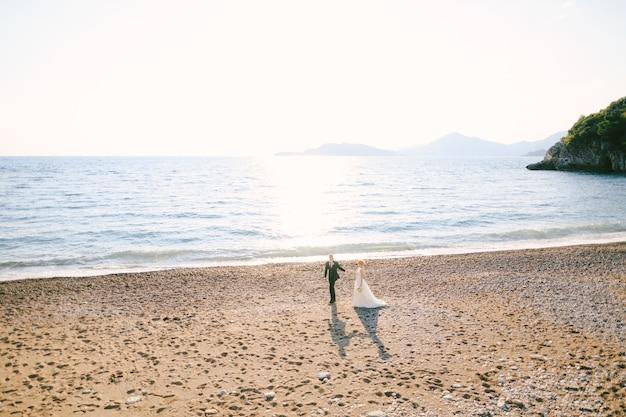 하얀 드레스를 입은 신랑과 신부가 손을 잡고 꽃다발을 들고 해변을 걷고 있다