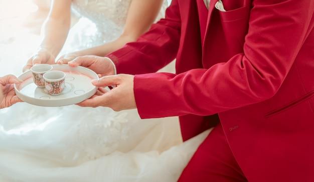 結婚式の日にお茶会で新郎と新婦。白いウェディングドレスと赤いスーツの新郎新婦が座って、ティーカップを持ち上げます。結婚または結婚。カップル生活を始めましょう。