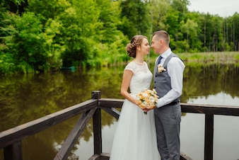 Groom and bride in wedding dress gainst a wooden verandah on the lake.