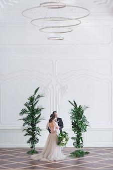 Жених и невеста со свадебным букетом держат друг друга за руки