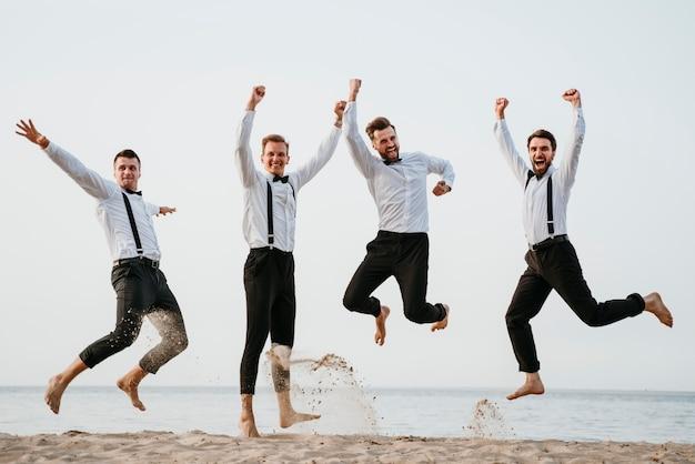 해변에서 점프하는 신랑과 그의 친구들