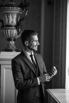 미소하고 호텔 홀에서 신부를 기다리는 결혼식 날 신랑. 의상과 나비 넥타이의 우아한 부자.