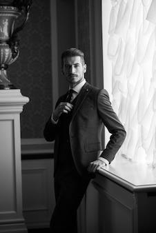 Жених в день свадьбы улыбается и ждет невесту в холле отеля. элегантный богатый мужчина в костюме и галстуке-бабочке.