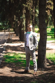 Жених в свадебном смокинге улыбается и ждет невесту. богатый жених в день свадьбы. элегантный жених в костюме и галстуке-бабочке.