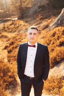 Groom in a black suit holds his hands in his pockets and looks at camera autumn