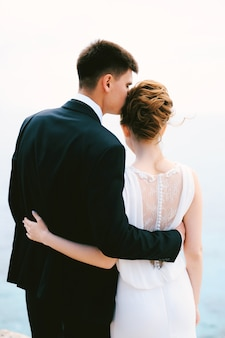 Groom in a black suit hugs and kisses bride in a white beautiful lace dress in the temple back view