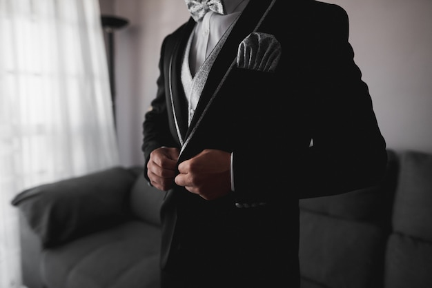Groom in black tuxedo and gray bow tie correctly putting on his jacket buttons