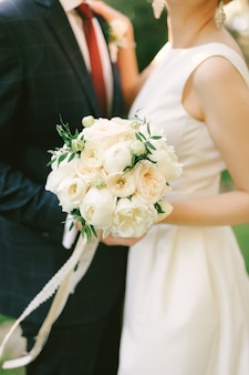 Groom in a blue checkered suit hugs bride in a white dress with a bouquet of flowers closeup