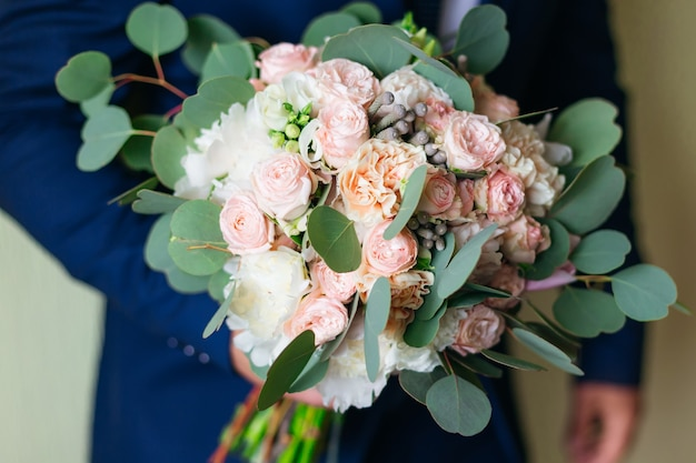 Groom in blue suit holds a beautiful wedding bouquet of roses.