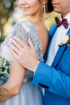 Groom in a blue suit hugs bride with a bouquet of flowers by the shoulders closeup