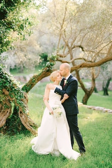 Groom in a blue suit hugs and kisses on the forehead bride in a white dress with a bouquet of