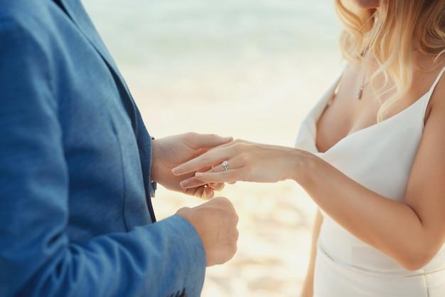 Lo sposo in tuta blu mette l'anello di nozze sulla mano della sposa in piedi