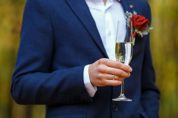 Groom in blue suit with red boutonniere hold in his hands wineglasses with champagne
