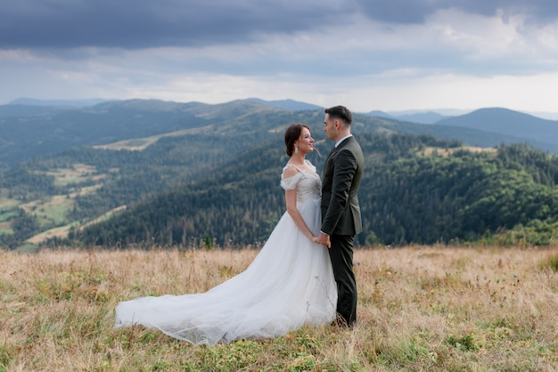 Groom and bride are standing in front of each other on the top of  a  hill in the summer mountains