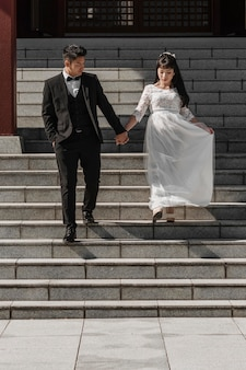 Groom and bride coming down the stairs