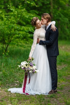 Groom and bride holding wedding bouquet with lilac flowers in vegetation background