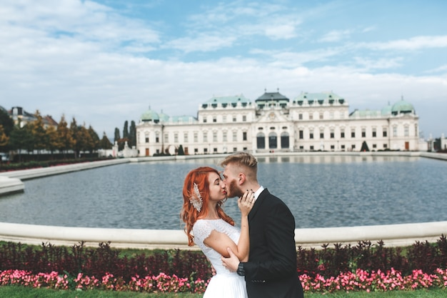 Groom and bride kissing in front of a fountain